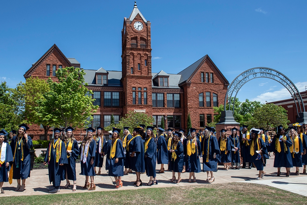 photo of uco graduates walking by Old North