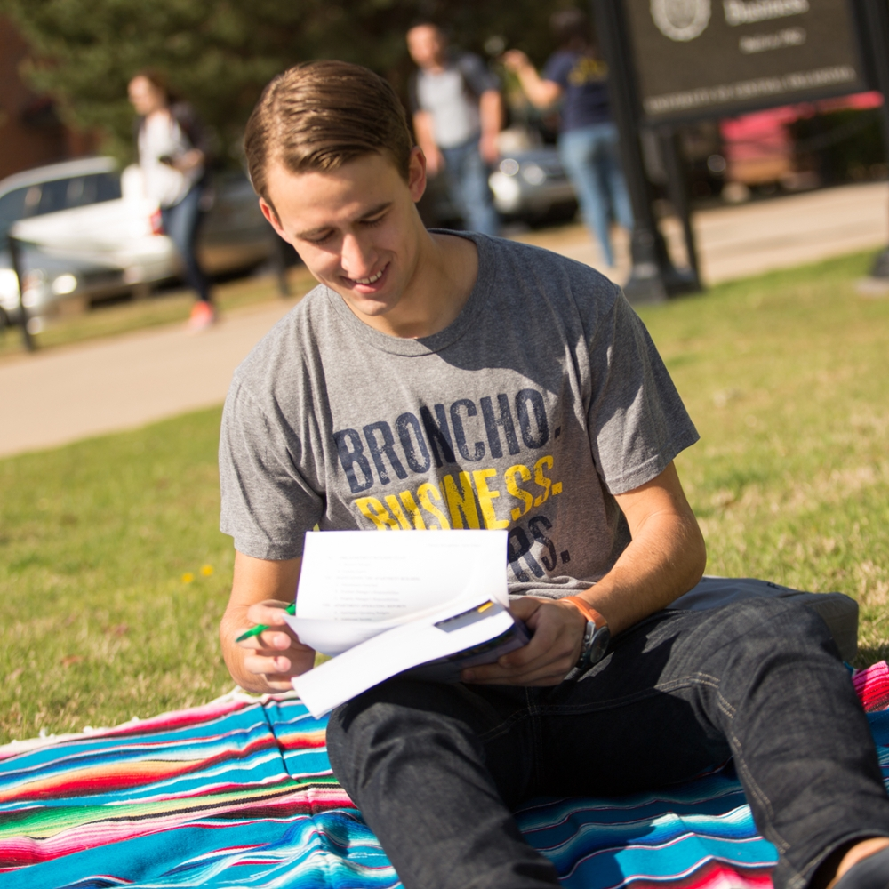 student sitting on ground outside studying