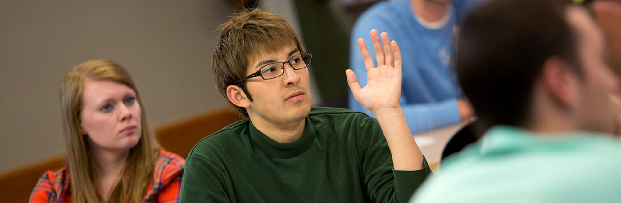 photo of a male student in class asking a question