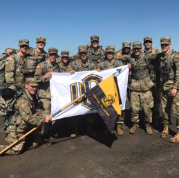 group of soldiers holding UCO flag