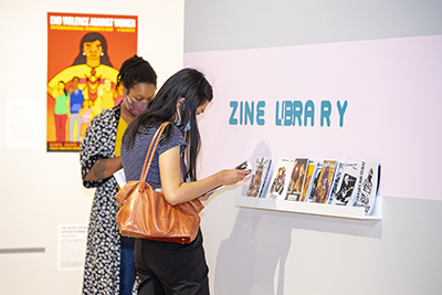 two women in the melton gallery looking at magazines created in the zine library.