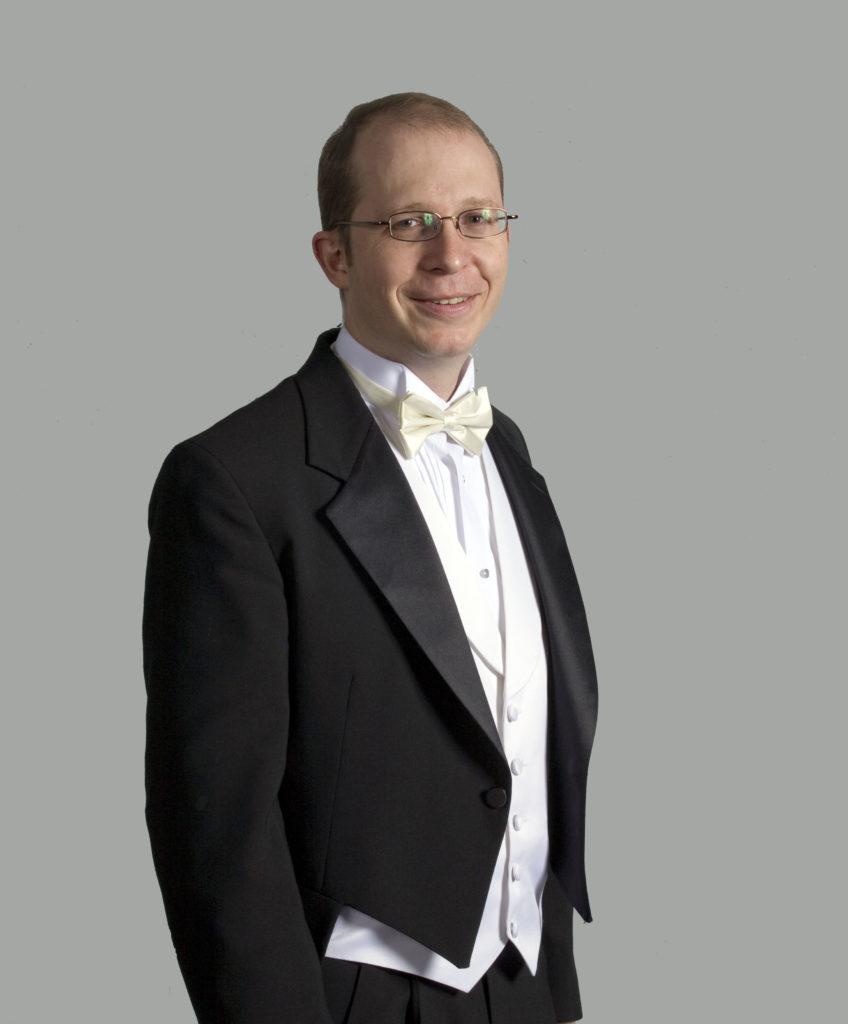 portrait of Alexander Tutunov standing in a black tuxedo