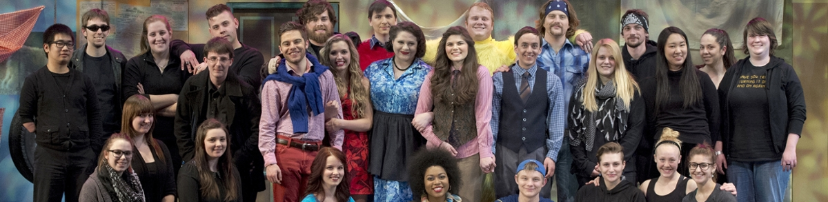 group photo of theatre arts students in front of a background set