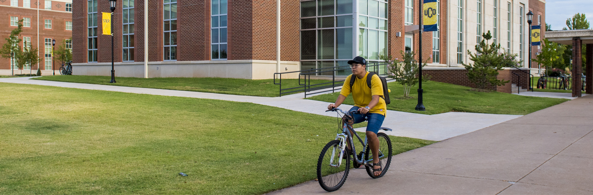 student bicycling on campus