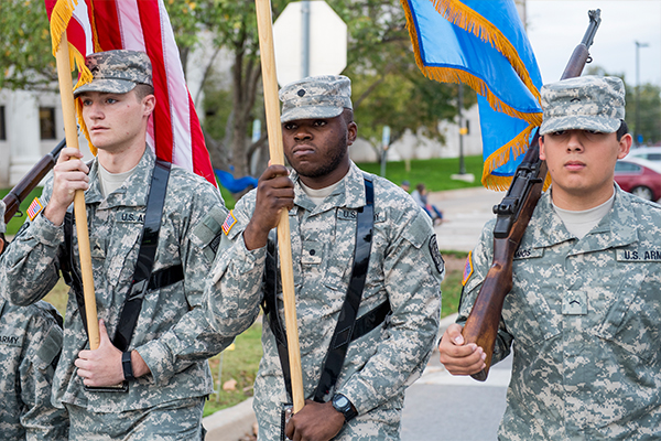 ROTC students marching and carrying flags