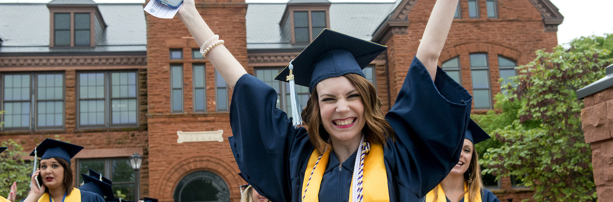 UCO Student in cap and gown with big smile