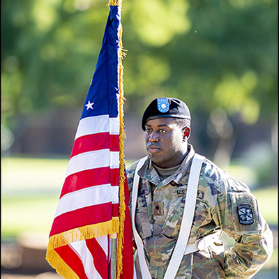 photo of man wearing US military uniform holding USA flag