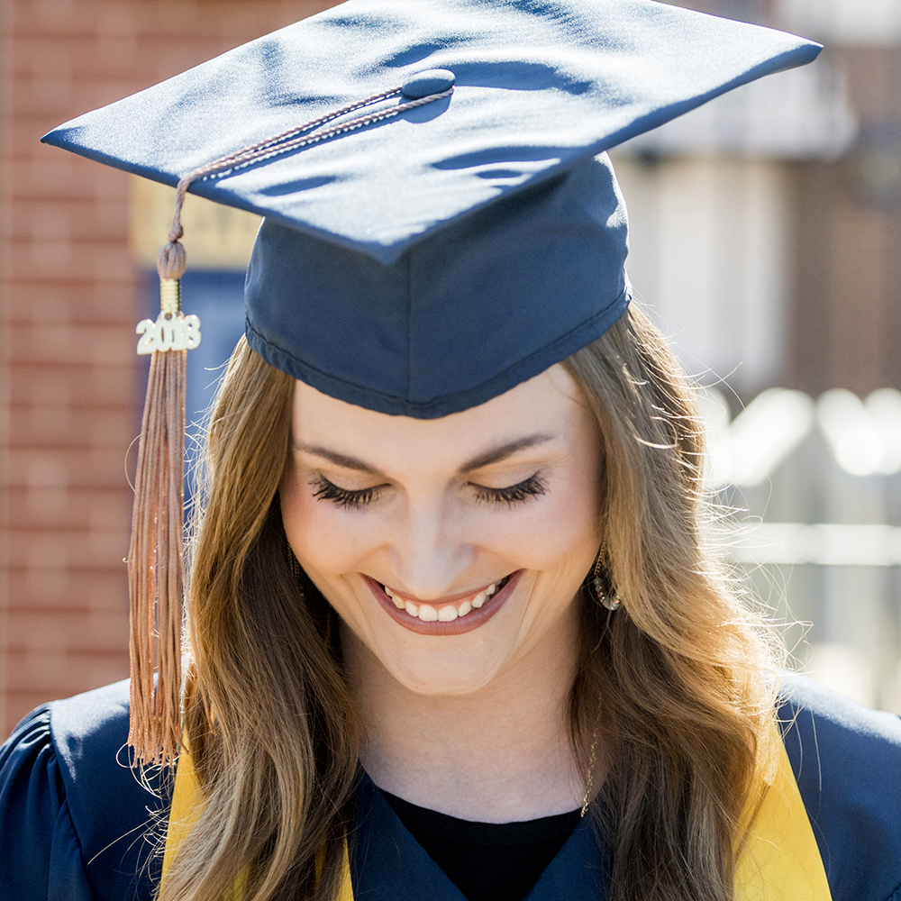 photo of a female uco student in cap and gown smiling