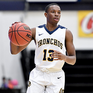photo of male uco basketball player dribbling