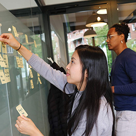 two people putting sticky notes on board