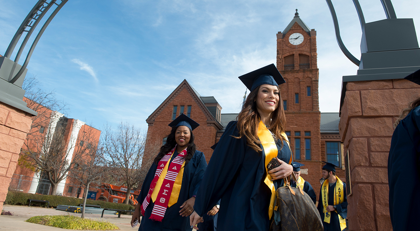 graduates stand in front of old north in regalia