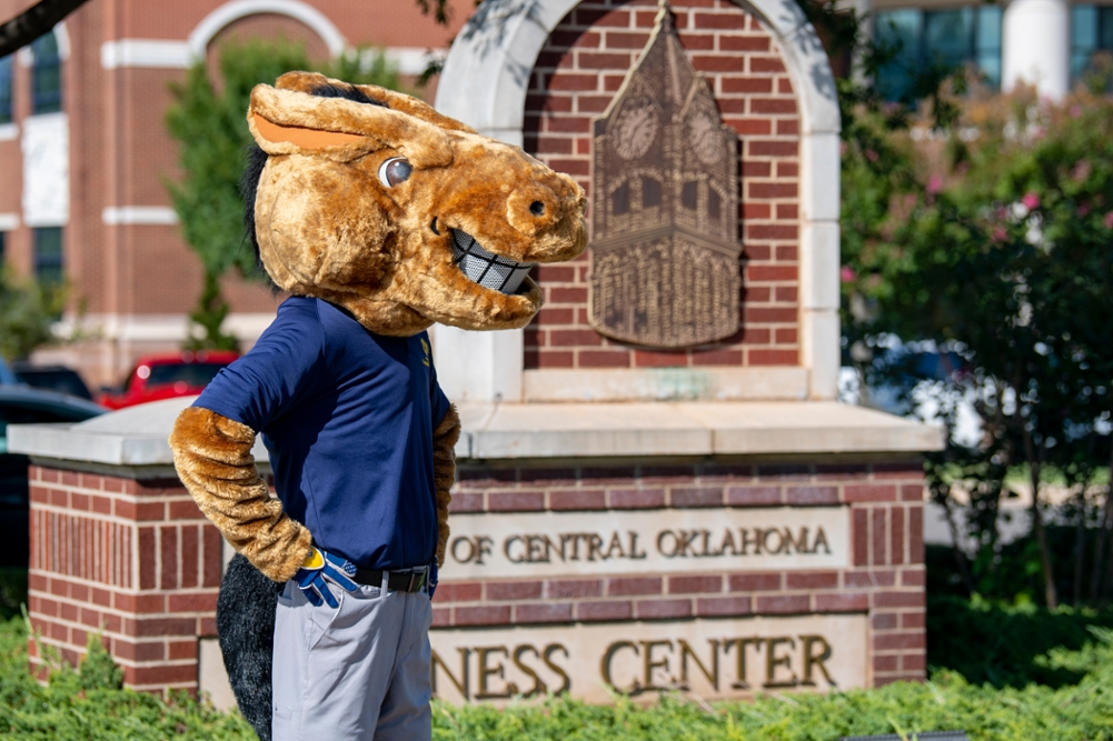Buddy the Broncho in front of the Wellness Center sign