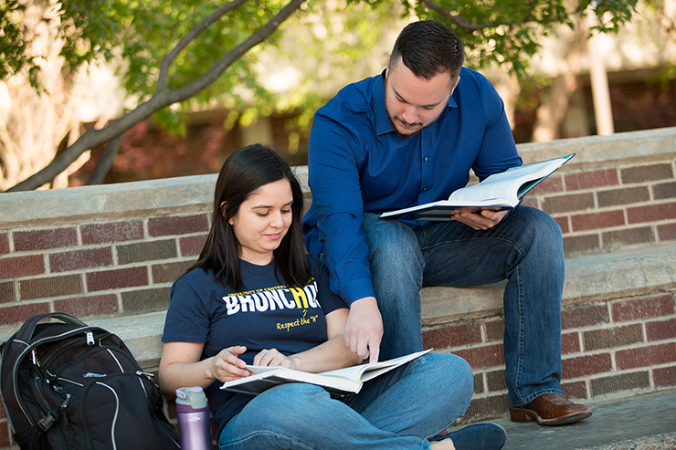 two students studying together outside