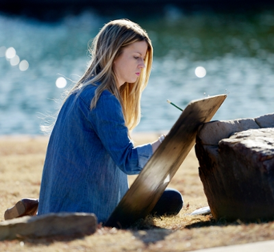 young woman drawing in front of water