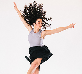 photo of a female dancer displaying proper hand placement against a cream background
