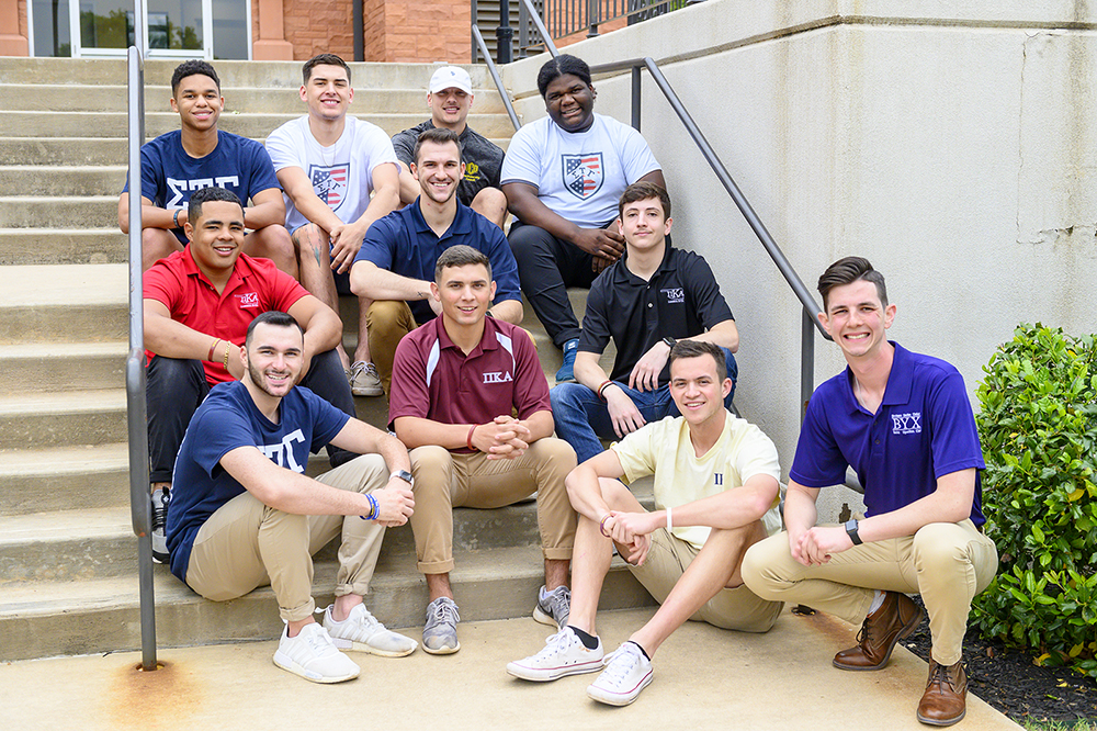 group of male students sitting on stairs
