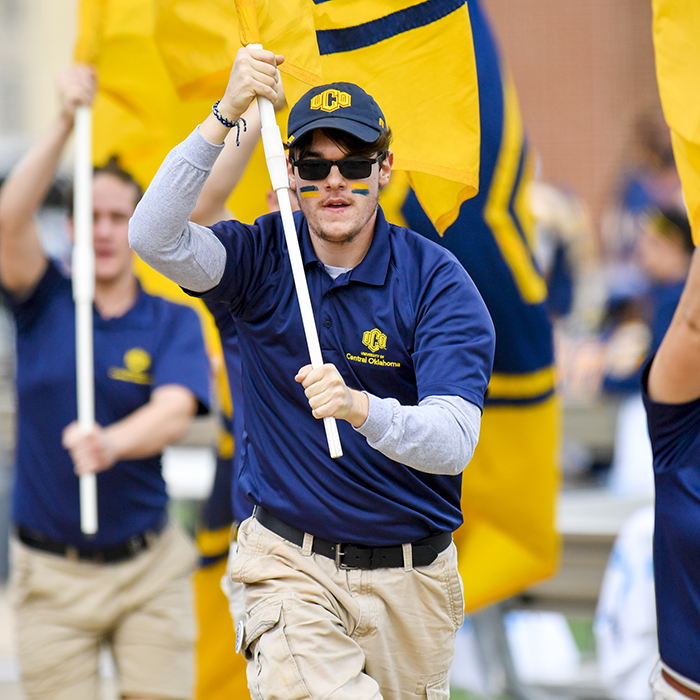 photo of uco student holding UCO flag and running on field