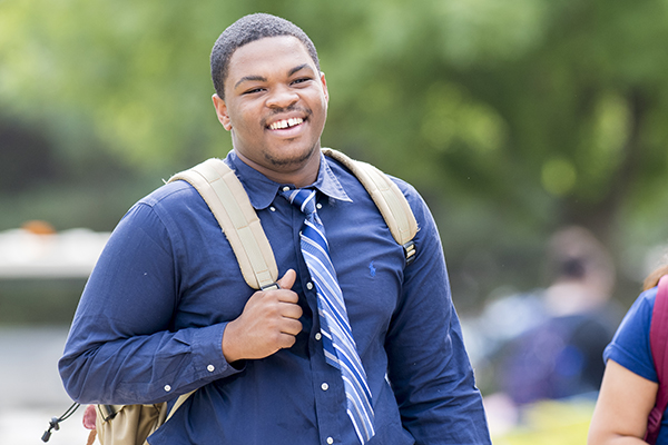 student wearing a tie smiling