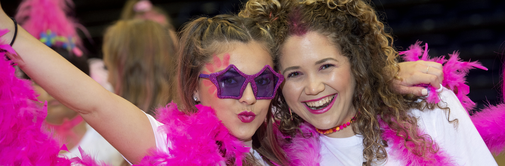Two girls smiling with pink feather scarf
