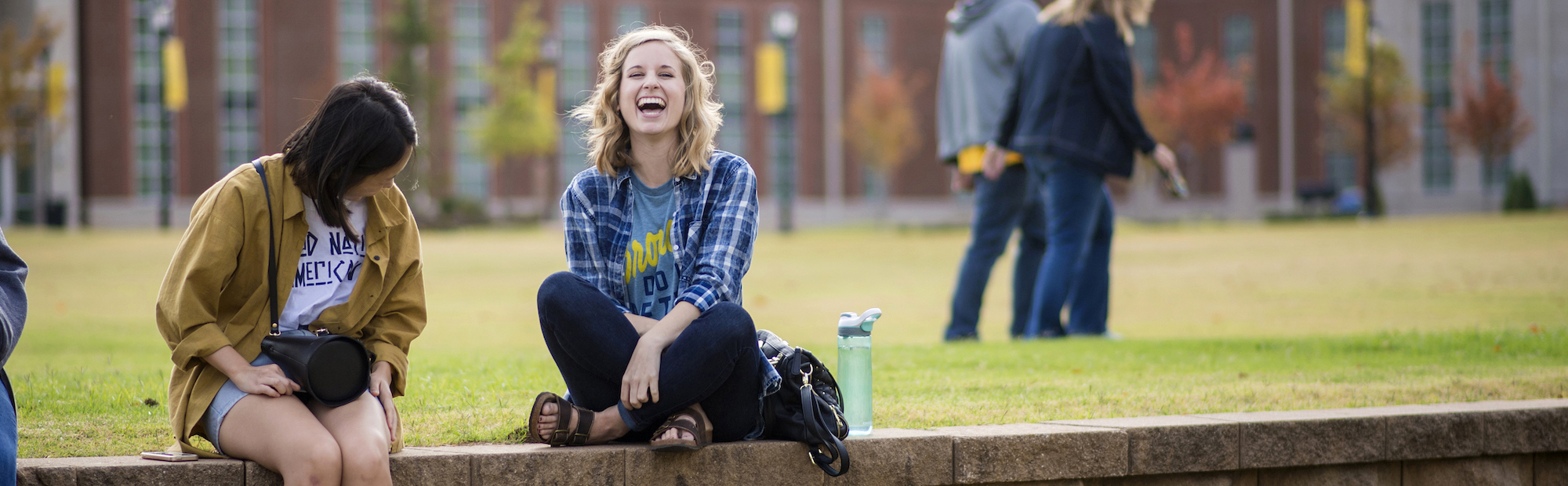 girls laughing in front of The Quad