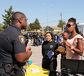 police officer speaking with students outside at information fair